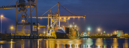 unloading: unloading cargo ship with containers in sea port at night Editorial
