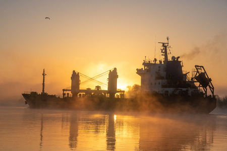 merchant ship sailing down the river in the mist at sunrise