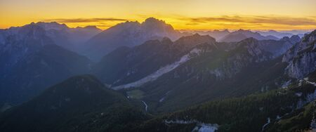 Panorama of the Julian Alps at sunset from the Mangart peak, the Triglav peak visible in the central part of the frame