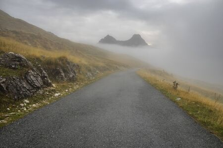 Mountain road in the Durmitor park in Montenegro on a cloudy, foggy morning 写真素材