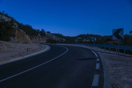 A winding mountain road at night illuminated by the light of the full moon Standard-Bild - 131947667