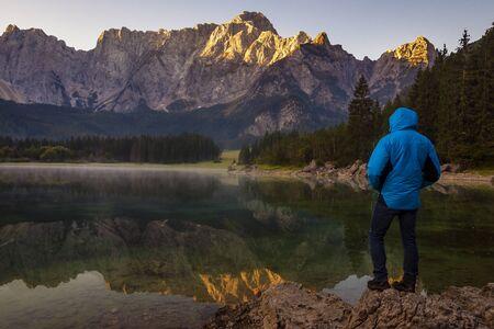 traveler admiring the alpine lake during sunrise Standard-Bild - 132235321