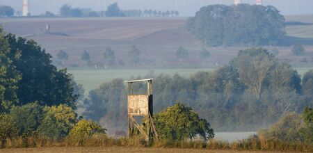Hunting tower against the background of autumn fields shrouded in morning fog 写真素材