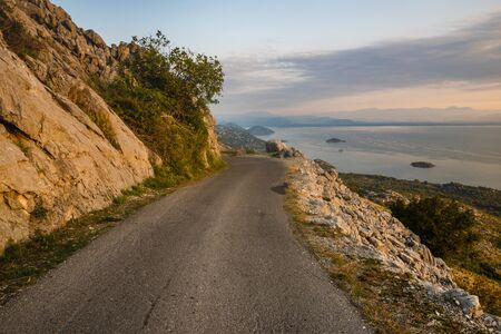 a narrow, winding road that runs on the edge of a cliff above Lake Skadar in Montenegro 写真素材