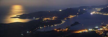 Kotor Bay in Montenegro at night in full moon light. Kotor lights visible