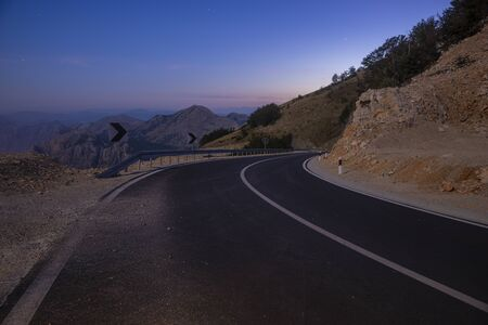 A winding mountain road at night illuminated by the light of the full moon 写真素材