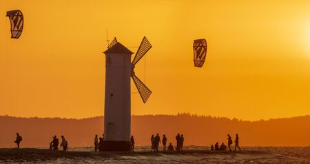 lighthouse in the shape of a windmill in Swinoujscie in Poland during sunset