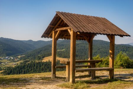 covered gazebo with table and benches overlooking the mountains
