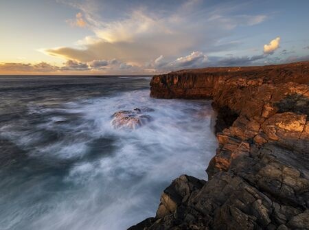 beautiful and dramatic sunset on a craggy rocky cliff, Jandia Peninsula, Fuertaventura Standard-Bild - 141104649