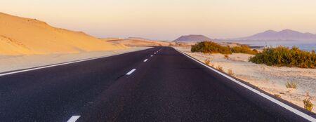 asphalt road running through sandy deserts Standard-Bild