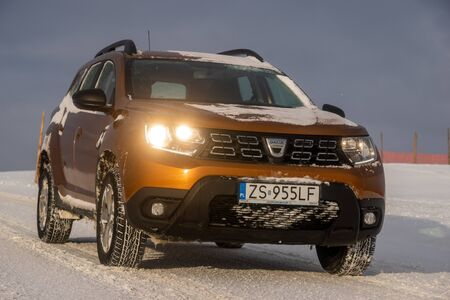Dacia Duster SUV when driving on a snowy road Standard-Bild - 141810694