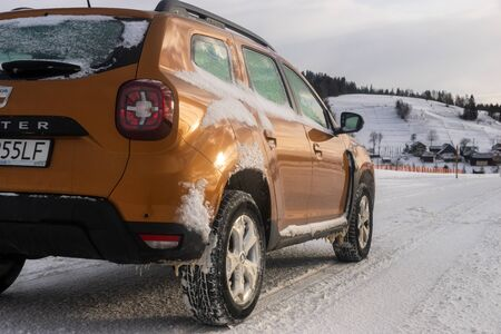 Dacia Duster SUV when driving on a snowy road Standard-Bild - 141810695