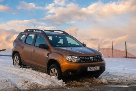 Dacia Duster SUV at the exit of the snowy mountain wilderness on the asphalt path Editorial