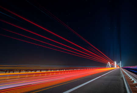 light traces of cars driving along the road at night through a beautiful modern highway bridge
