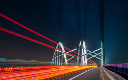 light traces of cars driving along the road at night through a beautiful modern highway bridge Standard-Bild - 159781478
