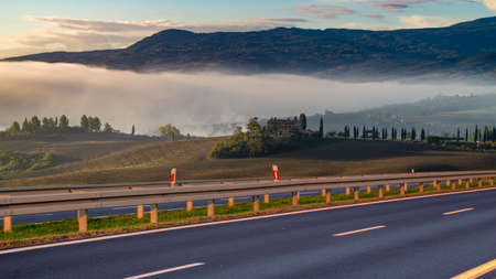 Beautiful scenic road with the Italian Tuscany landscape in the background