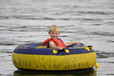 float tube: Young boy at the lake in a float tube Stock Photo