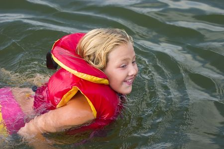 lifejacket: Young girl swimming with a lifejacket on Stock Photo
