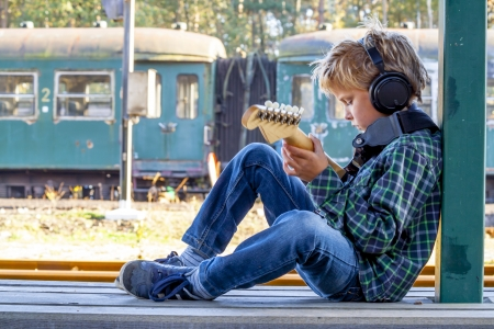 kid playing guitar at old railroad station