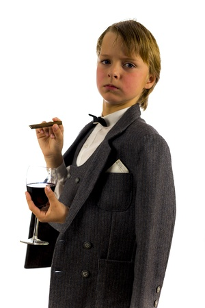 boy in tuxedo, with glass of red wine and a cigar, high key image photo
