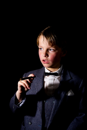 boy in suit, holding a cigar  low key image  photo