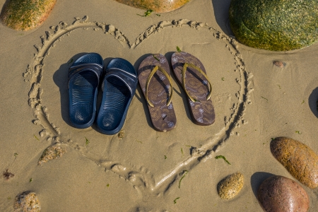 a pair of male and a pair of female footwear standing in heart shape on the beach photo