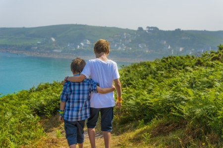 kids walking towards the sea, at a beautiful bay in normandy. photo