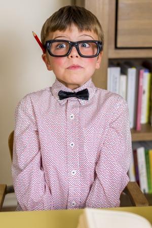 expresiones faciales: peque�o muchacho nerd con gafas geek, haciendo expresiones faciales Foto de archivo