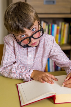 little nerdy boy with geeky goggles, writting in a book Stock Photo - 21954189