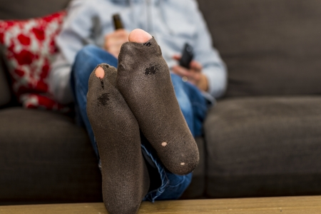 lazy man with holes in his socks hanging on his couch