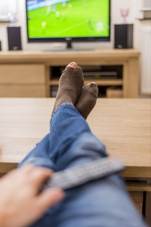 couch potato: man with holes in his socks watching soccer