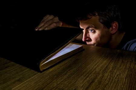 man peeking in a book filled with light