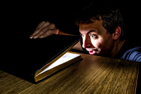 man looking surprised at a light inside a book