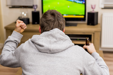 man cheering for soccer goal on tv Stock Photo