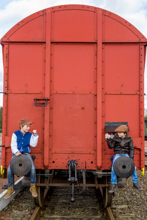 two kids secretly take a ride on the back of a train