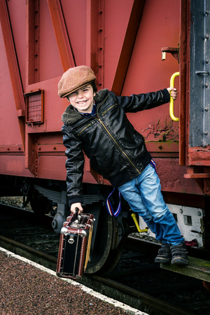boy hanging on the side of a train, with instagram style effect added