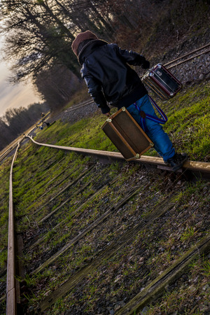 boy with suitcases following train rail to his destination photo