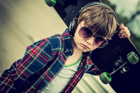 ni�os malos: fresco buscando chico del skate, con gafas de sol y el efecto de los auriculares de la vendimia a�adido Foto de archivo