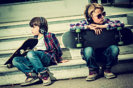 two cool skaters resting on stairs photo