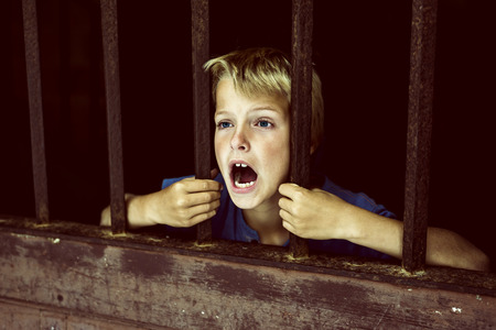 kid behind bars, screaming for help