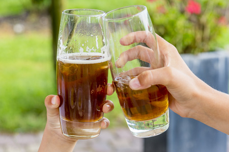 two kids hands toasting with their drinks, shallow depth of field