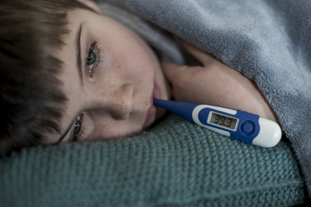celcius: sick little boy with thermometer in his mouth