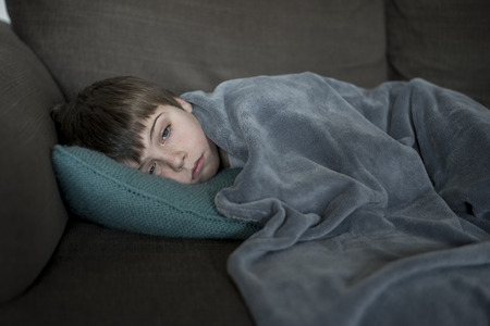 sick little boy laying on the sofa Stock Photo