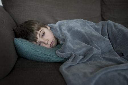 sick little boy laying on the sofa Фото со стока