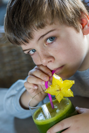 boy with a glass of healthy green juice