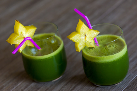 spinage: two green smoothies with a slice of a carambola