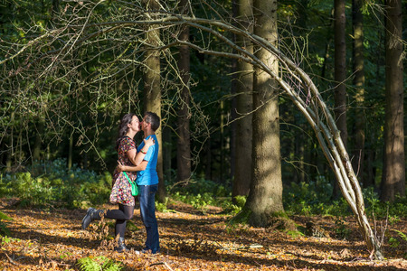 underneath: romantic couple kissing underneath a three in a forrest Stock Photo