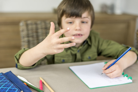 fingers: boy making homework, counting on his fingers Stock Photo