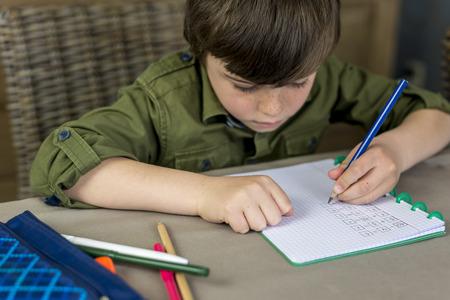 exemplary: boy working hard on his homework, shallow depth of field