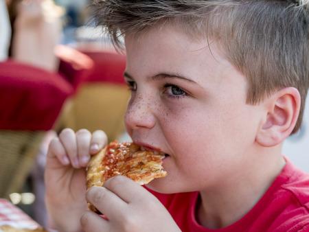 freckle: close up portrait of a little boy eating a pizza slice